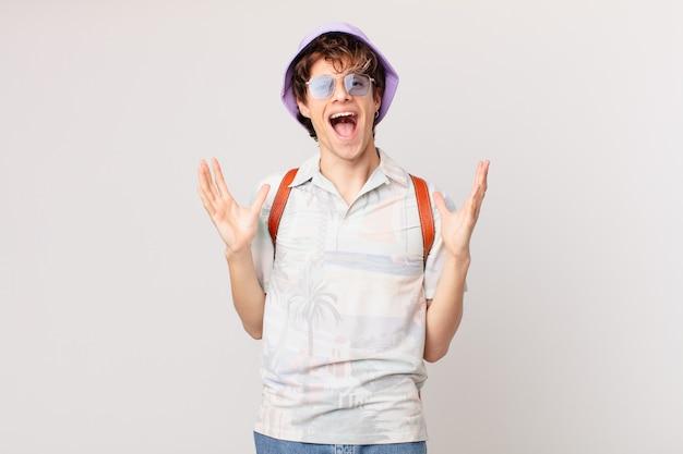Junger reisender oder touristenmann, der glücklich und erstaunt über etwas unglaubliches fühlt