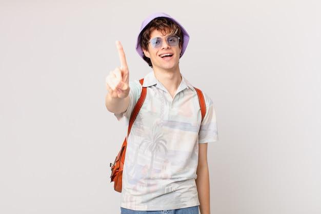 Junger reisender oder touristenmann, der stolz und zuversichtlich lächelt und nummer eins macht