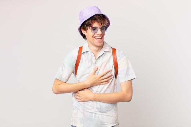 Junger reisender oder touristenmann, der über einen lustigen witz laut lacht