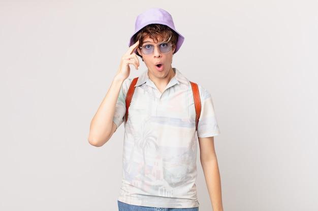 Junger reisender oder touristenmann, der überrascht schaut und einen neuen gedanken, eine neue idee oder ein neues konzept verwirklicht