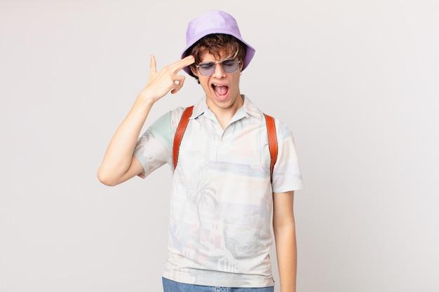 Junger reisender oder touristenmann, der unglücklich und gestresst schaut, selbstmordgeste, die waffenzeichen macht