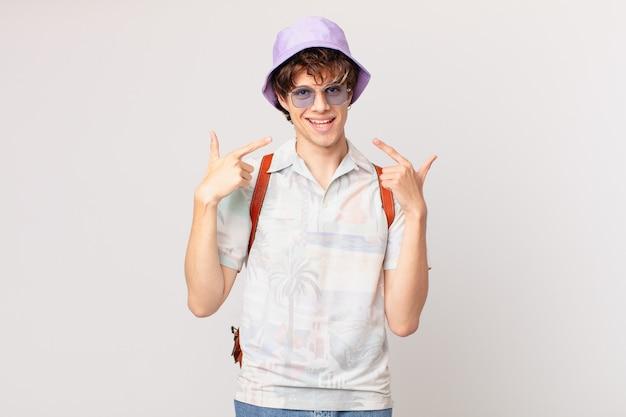 Junger reisender oder touristenmann, der zuversichtlich lächelt, um eigenes breites lächeln zu zeigen