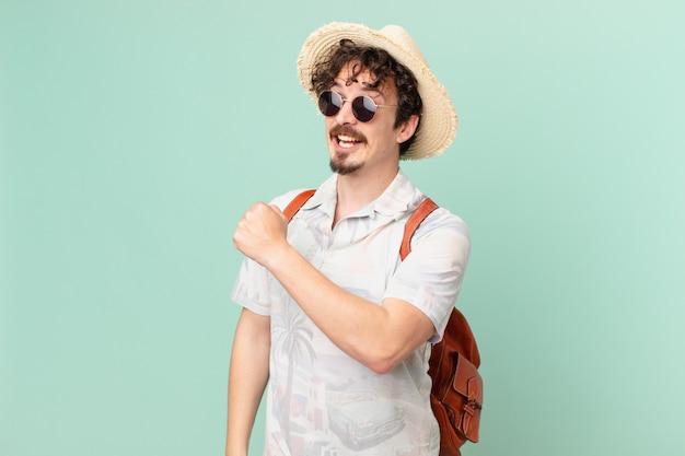Junger reisender tourist, der sich glücklich fühlt und einer herausforderung gegenübersteht oder feiert