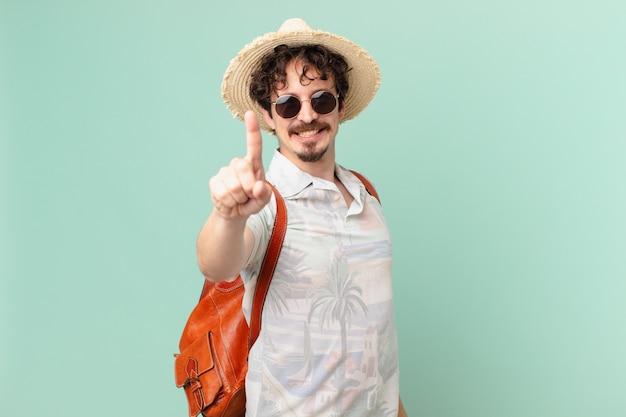 Junger reisender tourist, der stolz und zuversichtlich lächelt und nummer eins macht