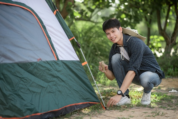 Junger reisender verwendet einen stein, um beim campingausflug im sommerurlaub auf die zeltheringe im wald zu schlagen