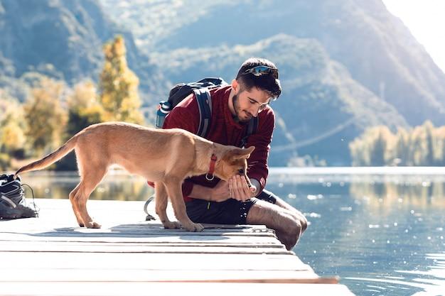 Junger reisender wanderer mit rucksack, der dem hund auf dem see wasser gibt.