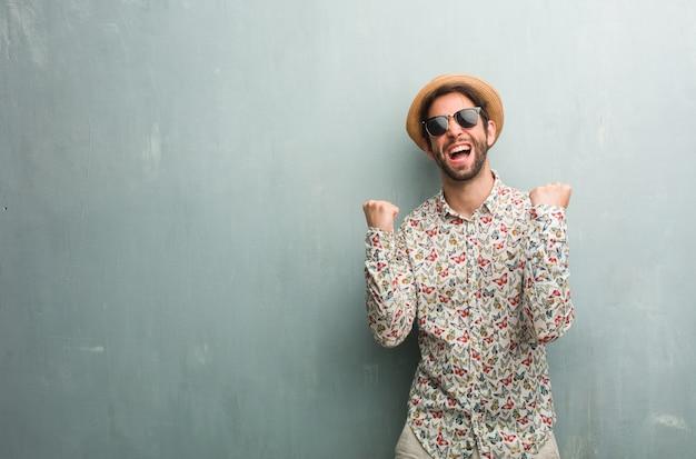 Junger reisendmann, der ein buntes hemd sehr glücklich und aufgeregt trägt, arme anhebend