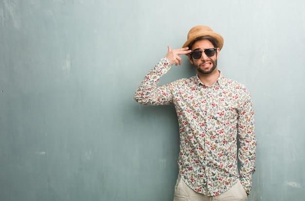 Junger reisendmann, der ein buntes hemd trägt, das eine selbstmordgeste macht, traurig und erschrocken glaubt, ein gewehr mit den fingern bildend