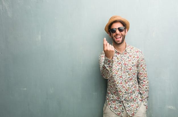 Junger reisendmann, der ein buntes hemd trägt, das einlädt, zu kommen, überzeugt und lächelnd, eine geste mit der hand machend