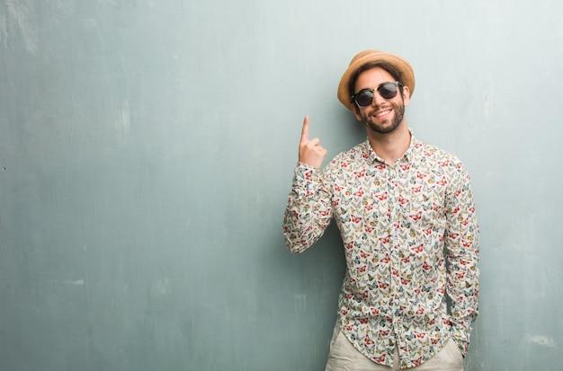 Junger reisendmann, der ein buntes hemd zeigt nummer eins, symbol der zählung trägt