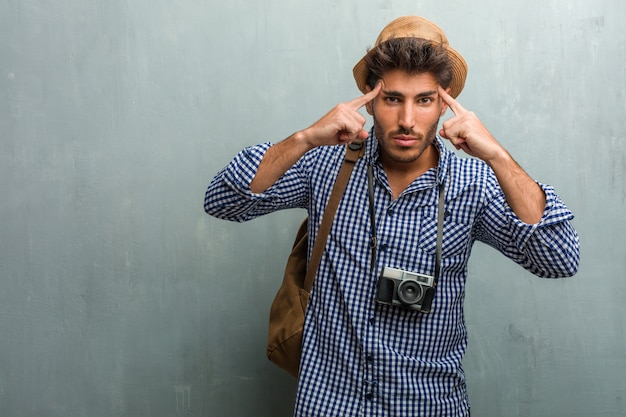 Junger reisendmann, der einen strohhut, einen rucksack und einen fotokameramann trägt, der eine konzentrationsgeste macht