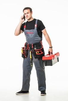 Junger reparaturmann spricht telefon mit werkzeuggürtel und kasten