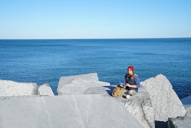 Junger reporter angeschlossen auf tablette durch den ozean
