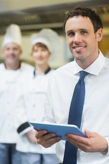 Junger restaurantmanager, der seine tablette hält