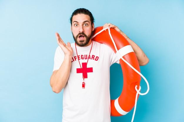 Junger rettungsschwimmermann, der einen rettungsschwimmer hält, isoliert überrascht und schockiert