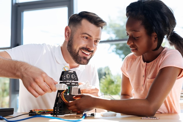 Junger robotiklehrer, der mit seinem schüler am tisch sitzt