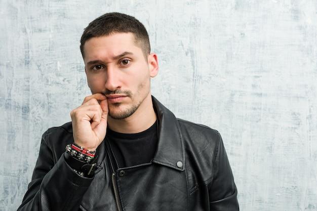 Junger rocker mann mit den fingern auf den lippen, die ein geheimnis halten.