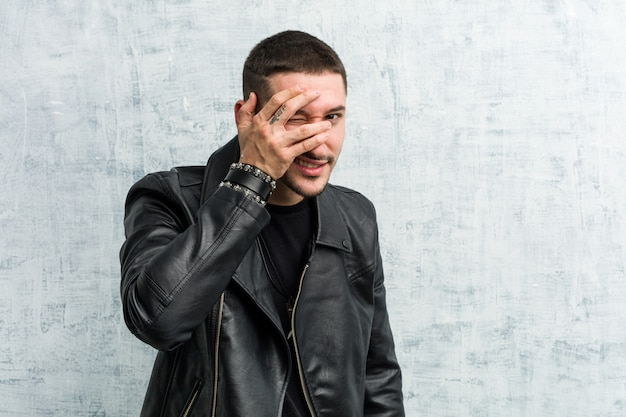 Junger rockermann blinzelt mit den fingern in die kamera, verlegenes deckgesicht