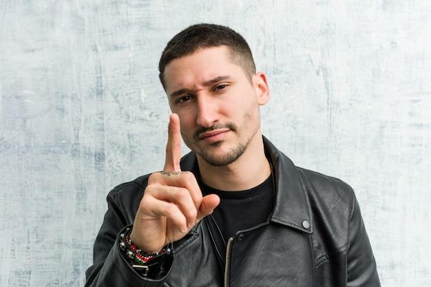 Junger rockermann, der nummer eins mit dem finger zeigt.