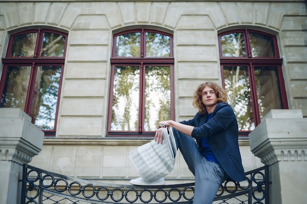 Junger rötlicher mann, der zeitung nahe altem artgebäude liest