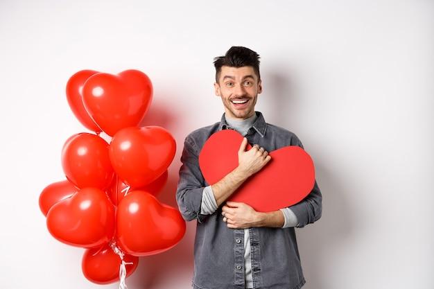 Junger romantischer mann, der mit liebe in die kamera schaut, valentinstag-herzkarte umarmt und glücklich lächelt, liebhaberfeiertag feiert, in der nähe von roten luftballons, weiß steht.