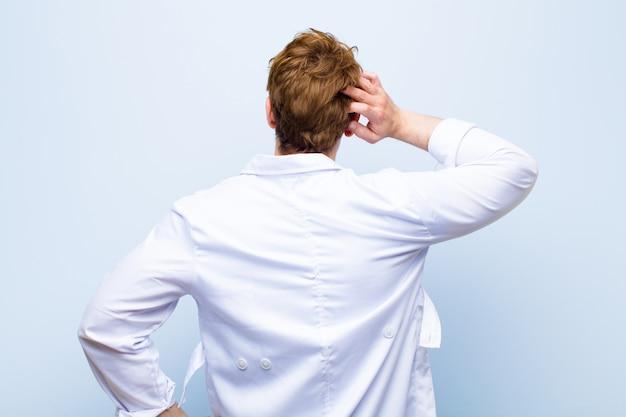 Junger roter chefarzt, der ahnungslos und verwirrt sich fühlt und eine lösung, mit der hand auf hüfte und anderer auf kopf, hintere ansicht gegen blau denkt