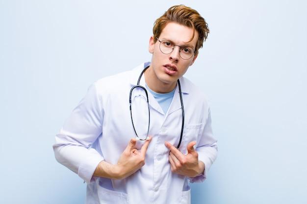 Junger roter chefarzt, der auf selbst mit einem verwirrten und fragenden blick zeigt