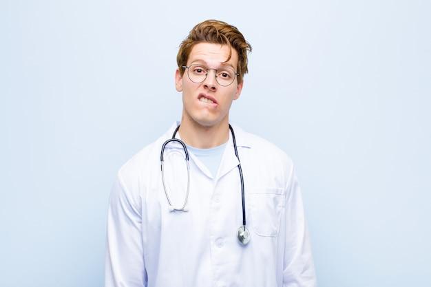 Junger roter chefarzt, der, beißende lippe mit einer nervösen geste verwirrt und verwirrt schaut und nicht die antwort auf das problem kennt