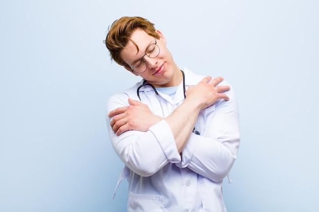 Junger roter chefarzt, der in liebe glaubt, selbst lächelt, streichelt und umarmt, einzeln bleibt, egoistisch und egozentrisch gegen blaue wand ist