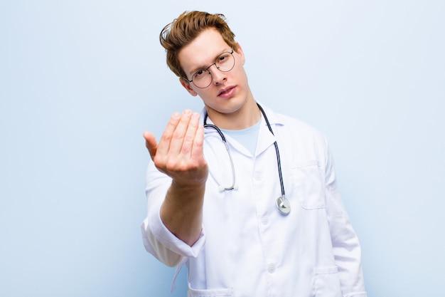 Junger roter chefarzt, der sich glücklich, erfolgreich und selbstbewusst fühlt, einer herausforderung gegenüberstehend und sagend, bringen sie es an! oder begrüßen sie gegen die blaue wand