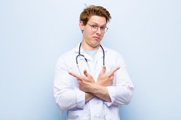Junger roter chefarzt, der verwirrt und verwirrt, unsicher schaut und in entgegengesetzte richtungen mit zweifeln gegen blau zeigt