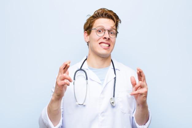 Junger roter hauptdoktor, der besorgt finger kreuzt und auf gutes glück mit einem besorgten blick gegen blaue wand hofft