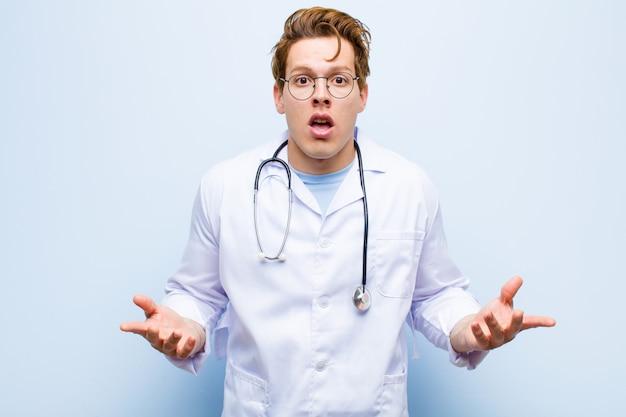 Junger roter hauptdoktor, der extrem entsetzt und überrascht, besorgt und in panik versunken ist