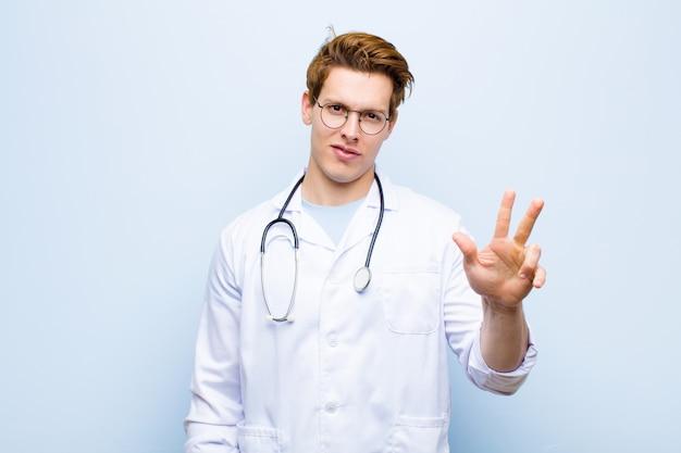 Junger roter hauptdoktor, der freundlich lächelt und schaut und nr. drei oder drittel mit der hand vorwärts zeigt und unten gegen blaue wand zählt