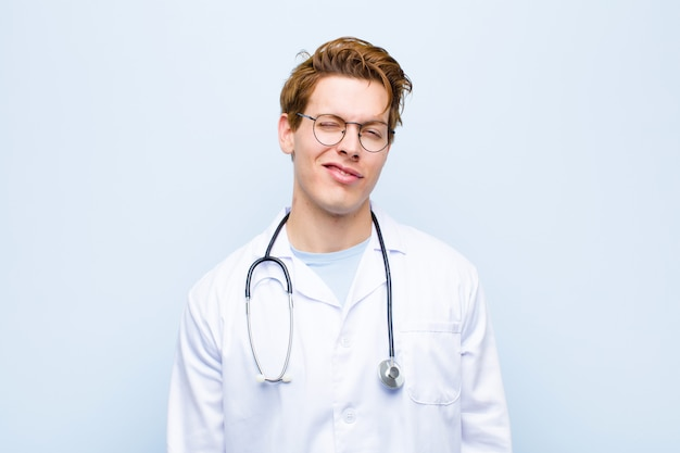 Junger roter hauptdoktor, der glücklich und freundlich schaut, ein auge lächelt und blinzelt