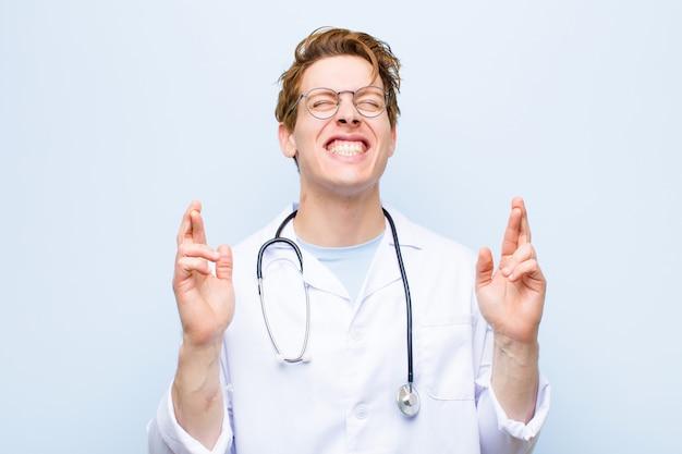 Junger roter hauptdoktor, der nervös und hoffnungsvoll sich fühlt, finger kreuzt, für gutes glück betet und hofft
