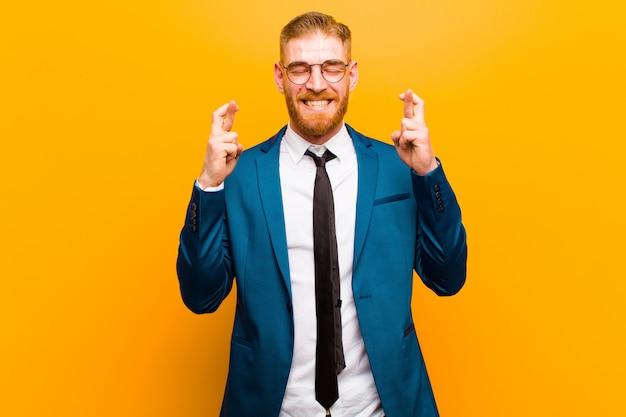 Junger roter hauptgeschäftsmann, der besorgt beide finger lächelt und kreuzt, gesorgt sich fühlt und gutes glück wünscht oder hofft