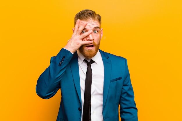 Junger roter hauptgeschäftsmann, der entsetzt, erschrocken oder erschrocken schaut, gesicht mit der hand bedeckt und zwischen fingerorangenwand späht