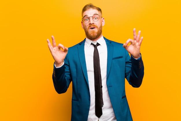 Junger roter hauptgeschäftsmann, der entsetzt, überrascht und überrascht sich fühlt und die zustimmung zeigt, die okayzeichen mit beiden händen gegen orange macht