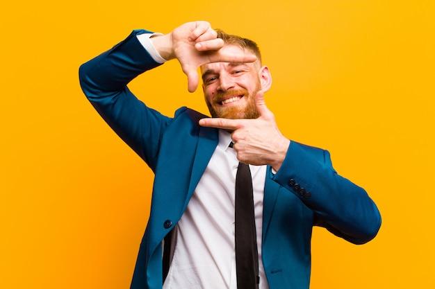 Junger roter hauptgeschäftsmann, der glücklich, freundlich und positiv sich fühlt, ein porträt oder einen fotorahmen mit den händen gegen orange lächelt und macht