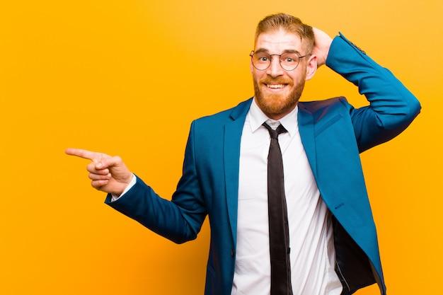 Junger roter hauptgeschäftsmann, der glücklich, positiv und überrascht, eine großartige idee verwirklichend schaut, die auf seitlichen kopienraum zeigt lacht