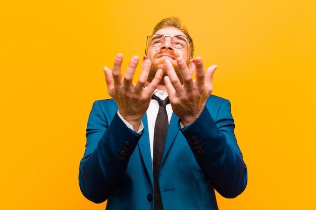 Junger roter hauptgeschäftsmann, der hoffnungslos und frustriert betontes unglückliches und gestörtes schreien und schreien gegen orange hintergrund schaut