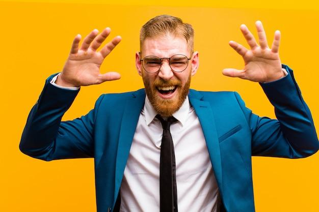 Junger roter hauptgeschäftsmann, der in der panik oder in der wut, entsetzt, erschrocken oder wütend, mit den händen nahe bei kopf gegen orange hintergrund schreit