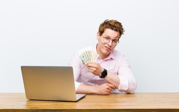 Junger roter hauptgeschäftsmann, der in seinem schreibtisch, geldkonzept arbeitet