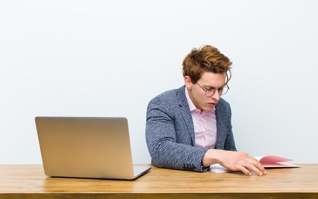 Junger roter hauptgeschäftsmann, der in seinem schreibtisch mit einem buch arbeitet