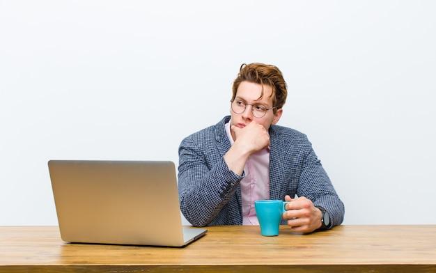 Junger roter hauptgeschäftsmann, der in seinem schreibtisch mit einer heißen kaffeetasse arbeitet