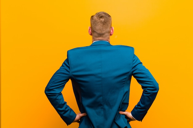 Junger roter hauptgeschäftsmann, der verwirrt oder voll oder die zweifel und fragen, wundernd, mit den händen auf hüften, hintere ansicht glaubt