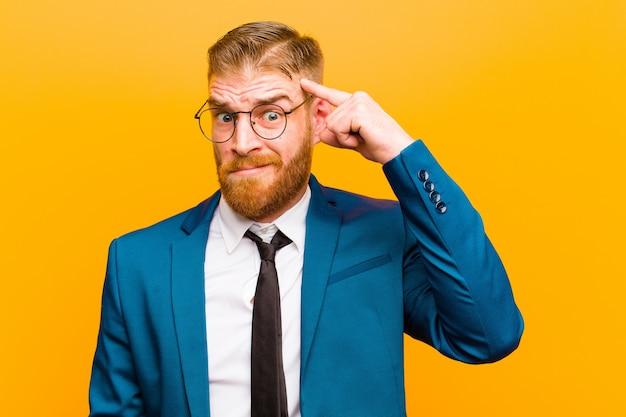 Junger roter hauptgeschäftsmann mit einem ernsten und starken blick, brainstorming und denken an ein schwieriges problem gegen orange