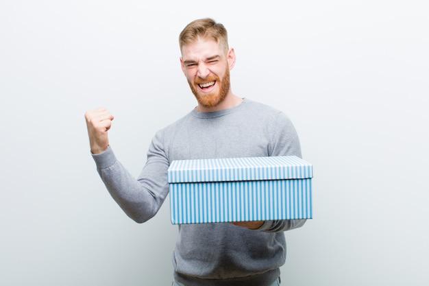 Junger roter hauptmann, der eine geschenkbox gegen weiß hält