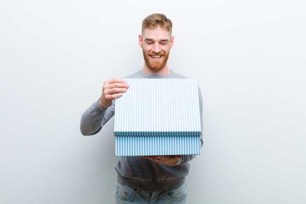 Junger roter hauptmann, der eine geschenkbox gegen weißen hintergrund hält